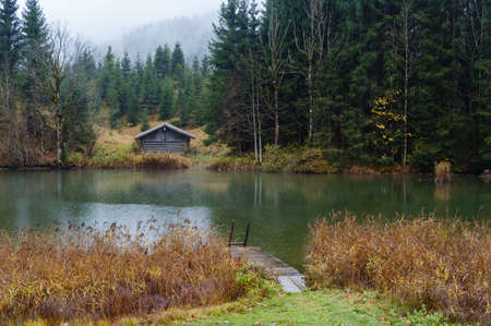 Alpine  lake Geroldee or Wagenbruchsee, Bavaria, Germany. Autumn overcast, foggy and drizzle day. Picturesque traveling, seasonal, weather, and rural nature beauty concept scene.