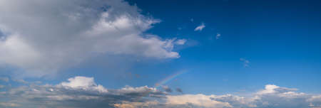 White cumulus clouds and rainbow in blue sky panoramic high resolution background