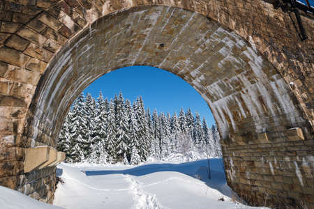 Stone viaduct (arch bridge) on railway through mountain snowy fir forest. Snow drifts  on wayside and hoarfrost on trees and electric line wires. Banco de Imagens