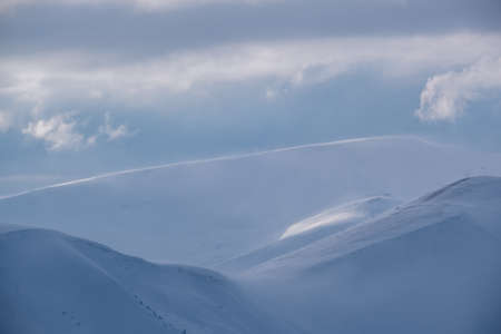 Snow covered winter mountains  in last evening sunlight. Magnificent windy dusk on tops above picturesque alpine ski resort Stok Fotoğraf