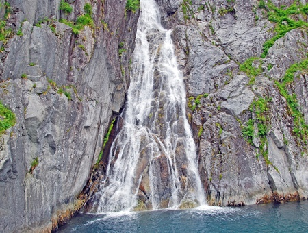 fjords: This waterfall is found rushing to the ocean from glaciers in Kenai Fjords National park