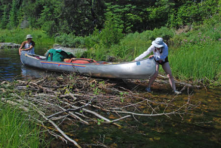 get across: These canoers are pulling their canoe across a beaver dam to get to Slate Lake