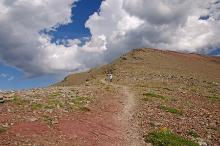 national scenic trail: Hiker heading down the scenic point trail in Glacier National park Stock Photo