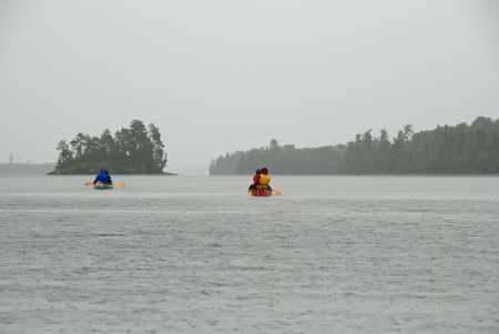 despite: This group of canoers are proceding into the wilderness despite the rain Stock Photo