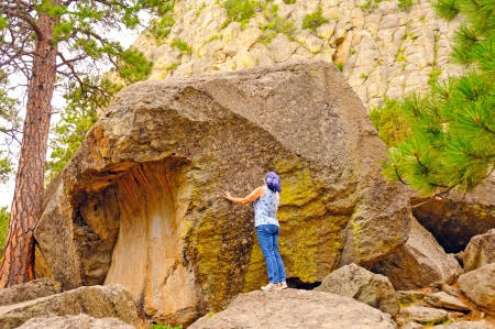 Woman Looking a a downed rock at Devils Tower in Wyoming Stock Photo - 16025139