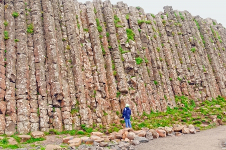 northern ireland: Person looking up at one wall of the Giants Causeway in Northern Ireland