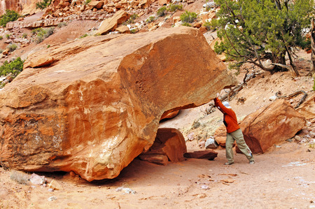 way out: Woman moving a Rock out of the way in Capital Reef National Park Stock Photo