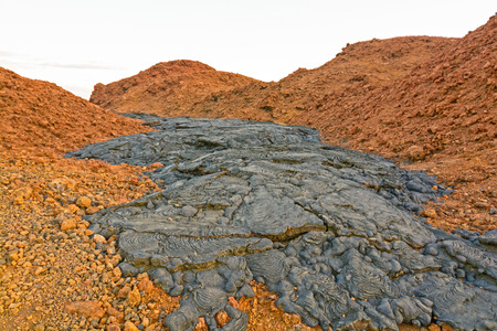 scoria: Black Lava Flow on Red Volcanic Ash on Santiago Island in the Galapagos Stock Photo