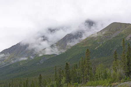 yukon territory: Fog and Clouds in the Mountains of the Yukon along the Alaska Highway Stock Photo