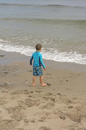 levantandose: El muchacho joven que sacara el valor para ir adentro en la playa del faro en la costa de Oregón