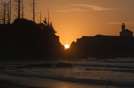 oregon coast: Sun Setting Between the Rocks on the Oregon Coast Stock Photo