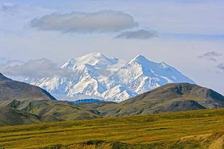 alaska scenic: Denali Appearing Above a Ridge in Denali National Park in Alaska Stock Photo
