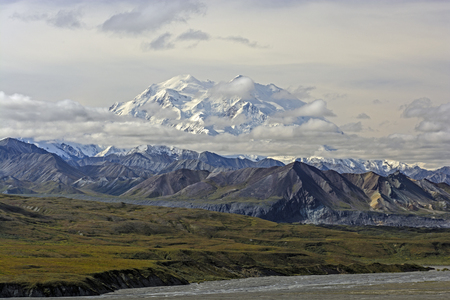 snow capped: Snow Capped Denali Peeking Through the Clouds near Eielson in Denali National Park in Alaska