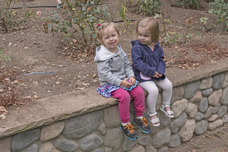 playmates: Little Girls Sitting in the Garden in California