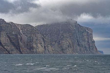 Looming Cliffs on a Coastal Fjord in Sam Ford Fjord on Baffin Island in Nunavut, Canada Фото со стока