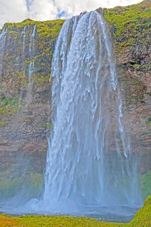 Shaded Seljalandsfoss Waterfall Roaring Over a Cliff in Iceland