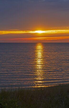 Sun Breaking Through the Clouds at Sunset on Lake Michigan near Montague, Michigan Фото со стока