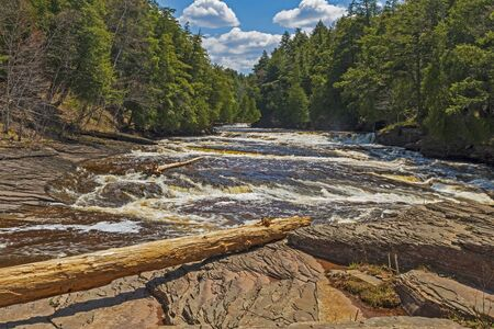 Raging River Flowing Past a Rocky Island on the Presque Isle River in Porcupine Mountains State Park in Michigan Stock Photo