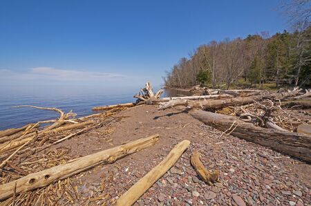 Battered Logs and Worn Rocks on a Calm Lake Superior shore in Porcupine Mountains State Park in Michigan