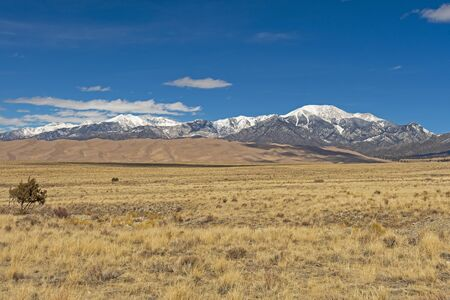 Looking across the Plains at Sand Dunes and Snowy Mountains in Great Sand Dunes National Park in Colorado