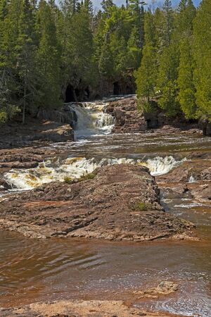 Powerfall Waters Cutting Through the Pines at Fifth Falls in Gooseberry Falls State Park in Minnesota 스톡 콘텐츠