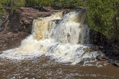 Spring Waters on Upper Goosebery Falls amidst Red Rocks in Gooseberry Falls State Park in Minnesota 스톡 콘텐츠