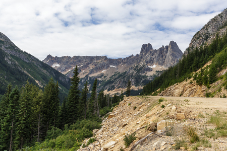 A mountain highway leading up to Washington Pass with Liberty Bell Mountain in the background.