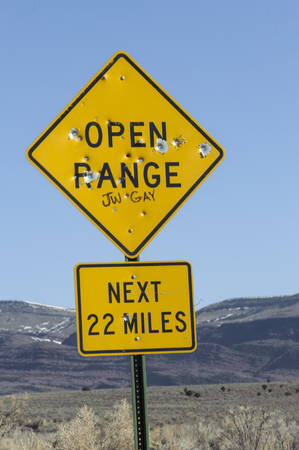 communications tools: Shot up road sign, Sand Wash Basin, Colorado, USA   Photo: Peter Llewellyn