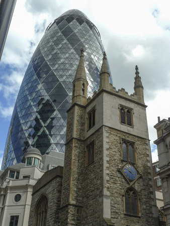 gherkin: The Gherkin with St. Andrew Undershaft in foreground, St. Mary Axe Street, London, England Editorial
