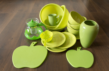 green dishes on a dark wood floor Stock Photo