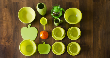 green porcelain dishes top view with an orange plastic funnel photo