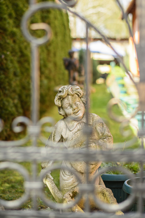 Cheerful statue of a boy in the garden. Stock Photo
