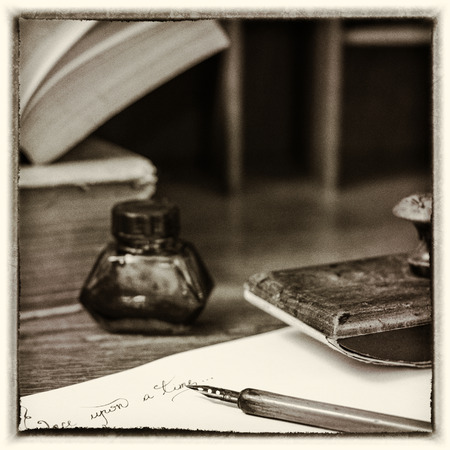 "Text ""Once upon a time"" written in ink. A fountain pen, an ink pot, a blotting paper holder and old books. Post processed to look like an old photo."