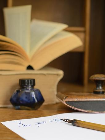 Zin Er was eens in inkt geschreven op papier, omringd met oude, stationaire en oude boeken. Stockfoto