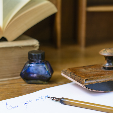 """Text """"Once upon a time"""" written in ink on paper sheet surrounded with a fountain pen, an ink pot, a blotting paper holder and old books."""