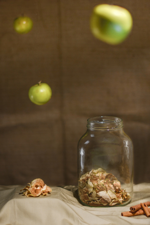 Dried apples with cinnamon. Arrangement with an old jar, cinnamon sticks and flying apples. Low key.