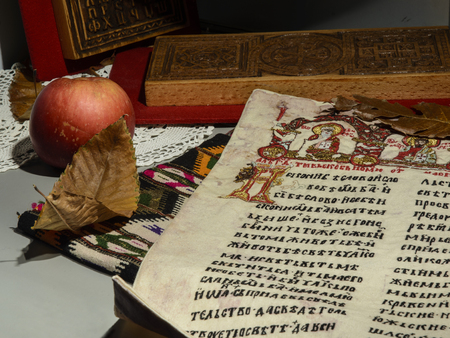 Page from The Miroslav Gospel embroidered on canvas. Wood carvings, red apple, dry leaves and partially visible crochet and kilim. Selective focus. Editorial