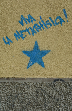 Long live the metaphysics! The text is written in Spanish language above the blue star painted on the dirty ochre and gray wall. A concept photograph. A post processed photograph.
