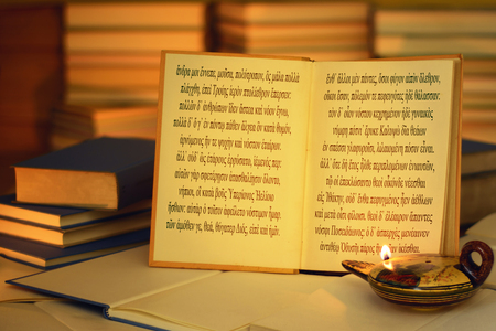 Open book illuminated by an oil lamp. The opening lines of The Odyssey written in the ancient Greek language. A stack of books. On the lamp, visible inscription Aphrodite in the Greek alphabet. Stock Photo
