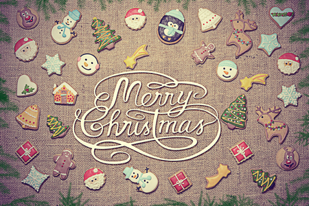 Merry Christmas! Christmas greeting written among decorative gingerbread cookies surrounded with fir branches. Vintage look added in post-processing.