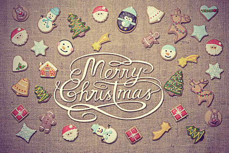Merry Christmas! Christmas greeting written among decorative gingerbread cookies. Vintage look added in post-processing.