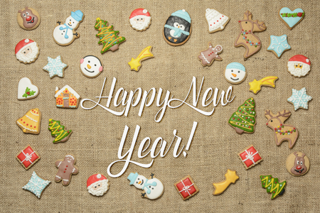 Happy New Year! Holiday greeting written among decorative gingerbread cookies.