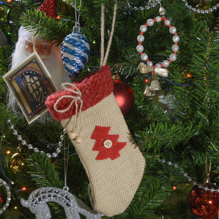 Christmas stocking and christmas tree decorations hanging on the christmas tree branches. Selective focus. Фото со стока