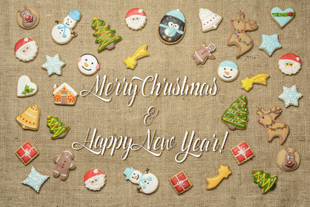 Merry Christmas and Happy New Year! Holiday greetings written among decorative gingerbread cookies. Фото со стока