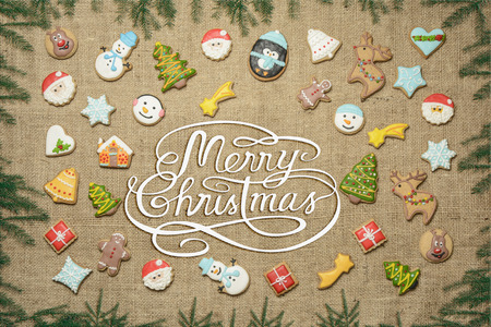Merry Christmas! Christmas greeting written among decorative gingerbread cookies surrounded with fir branches. Imagens