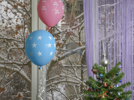 Winter birthday! Part of a decorated Christmas tree and two balloons. On purple balloon is written Happy birthday. Blurry branches of the Platanus tree covered with snow and part of a building.