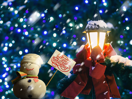 "Snowman figure holding a placard board with stick attached, with the text ""Merry Christmas!"" written on it. A street lantern wrapped in a red ribbon and fir branches. It is snowing. Beautiful bokeh."