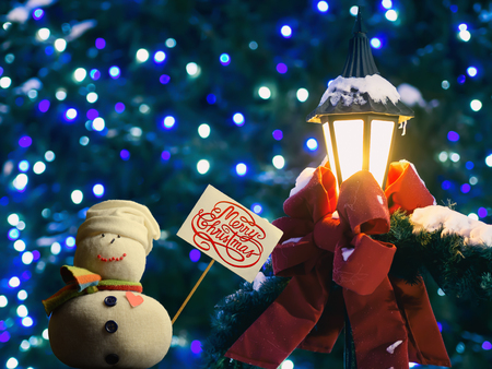 "Snowman figure holding a placard board with stick attached, with the text ""Merry Christmas!"" written on it. A street lantern wrapped in a red ribbon and fir branches. A beautiful bokeh in a background."