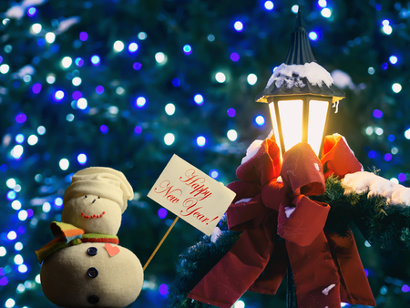 "Snowman figure holding a placard board with stick attached, with the text ""Happy New Year!"" written on it. A street lantern wrapped in a red ribbon and fir branches. A beautiful bokeh in a background."