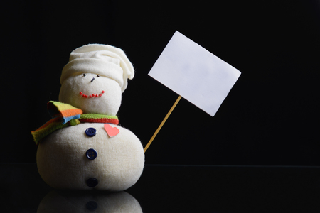 Snowman figure on a black background holding an empty placard board with stick attached. A contrasty low key photograph. Фото со стока